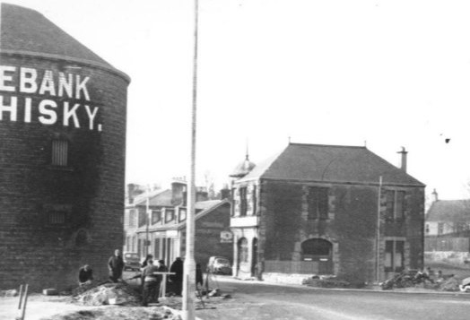 East End of Camelon Main Street facing West showing Rosebank Buildings directly behind Lamppost.  Bonded warehouse on the left.